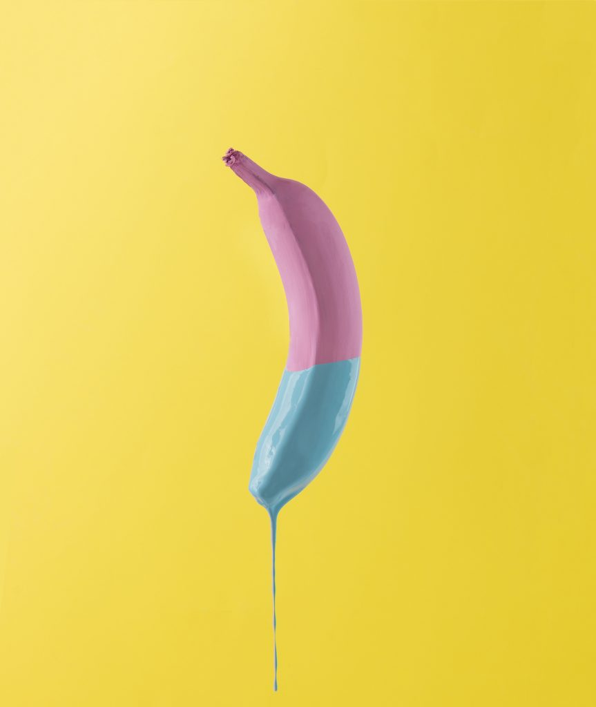 Pink banana with dripping blue paint on yellow background. Minimal food concept.