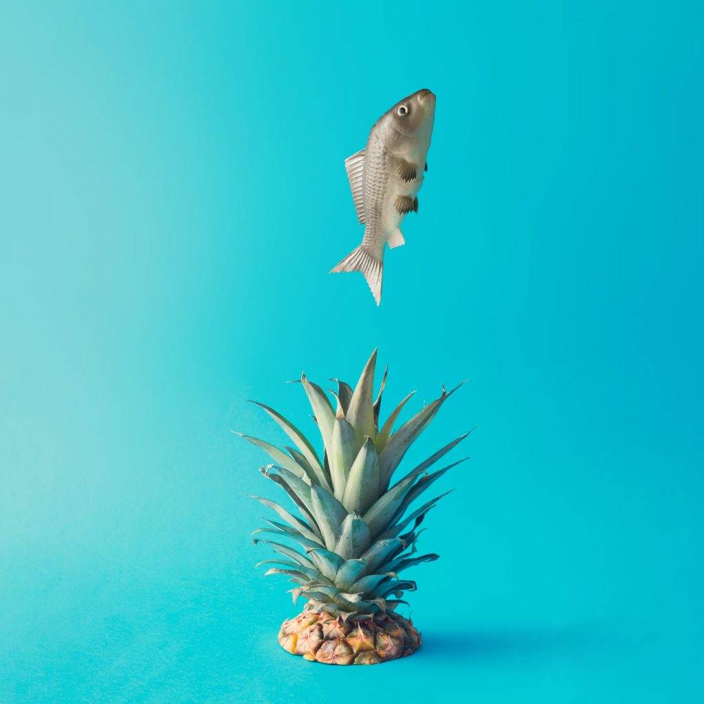 Fish jumping out of of water. Pineapple splash. Creative minimal food concept.