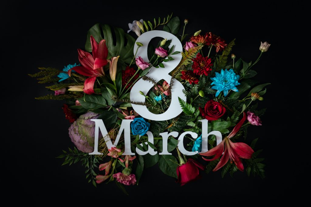 Colorful 8 March. Floral Greeting card. Happy Women's Day. Flower and leaves flat lay spring holiday background, space for text. Nature Trendy Design. Happy Mother's Day.