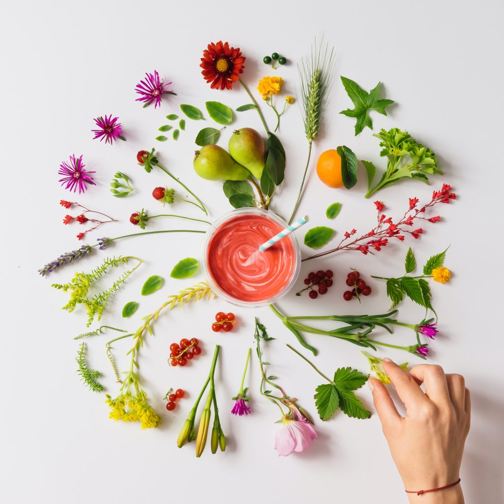 Various natural things neatly arranged in circle with homemade strawberry smoothie. Flat lay. Nature concept.