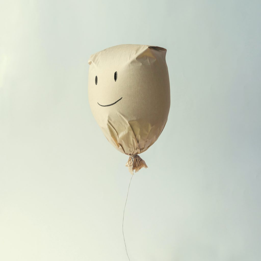 Paper bag balloon with smiley face emoji  on white background. Creative minimal concept.